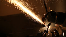 Sparks fly while the man cutting a metal rod with a grinding machine stock video