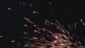 Sparks flying at night. Sparks flying from a metal grinding machine with pink, orange and green colors. Close up analog abstract shot stock video