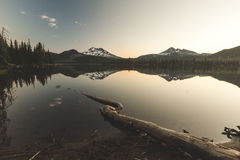 Sparks Lake Morning. Beautiful sunrise view of Sparks Lake near Bend, Oregon. Large tree root in foreground with two mountain peaks in distance. Morning, summer stock photography