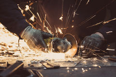 Sparks made by using a circular grinding tool on a metal surface in a workshop. Sparks made by using a circular grinding tool on a metal surface in a dark royalty free stock photo