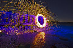 Sparks at night in cool blue water Royalty Free Stock Photos