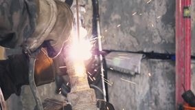 Sparks, and smoky by welding iron equipment near the wall. Frame. Close-up. stock video footage