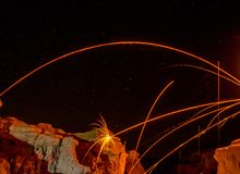 Sparks and arcs over cliff. Sparks and streaks from burning steel wool in night skies over cliff formations Royalty Free Stock Photography