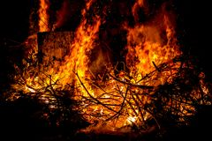 Sparks and tongues of fire on branches and trunks burning in a b. Ig bonfire Royalty Free Stock Photography