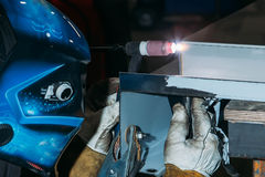 Sparks while welder uses torch to welding. In gloves Stock Photo