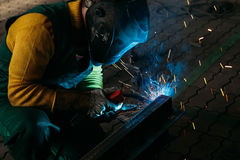 Sparks while welder uses torch to welding. In gloves Royalty Free Stock Photo