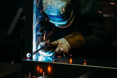 Sparks while welder uses torch to welding. In gloves Stock Photos