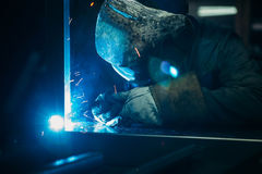 Sparks while welder uses torch to welding. In gloves Royalty Free Stock Photography