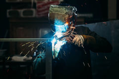 Sparks while welder uses torch to welding. Industry Royalty Free Stock Image