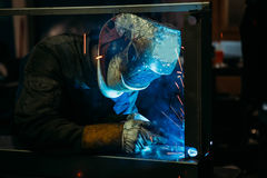 Sparks while welder uses torch to welding. Industry Stock Images