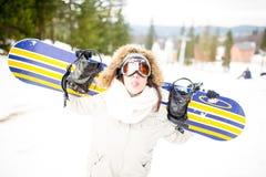 sparling Молодая красивая женщина при лыжная маска держа ее сноуборд на молодой женщине наклона лыжи в лыжном курорте Стоковая Фотография