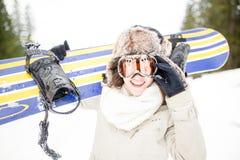 sparling Молодая красивая женщина при лыжная маска держа ее сноуборд на молодой женщине наклона лыжи в лыжном курорте Стоковые Изображения RF