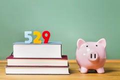 Sparplanthema mit 529 Colleges mit Lehrbüchern und Sparschwein Stockfotografie