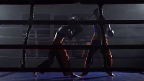 Sparring in the ring between two girls in a dark space. Slow motion