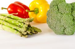 Sparris, saftiga röda och orange peppar med en grön svans ligger bredvid packe av grönsallat, och broccoli är på en vit bakgrund royaltyfria bilder