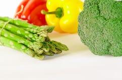 Sparris, saftiga röda och orange peppar med en grön svans ligger bredvid packe av grönsallat, och broccoli är på en vit bakgrund royaltyfria foton