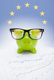 Sparschwein über Börsediagramm mit europäischer Flagge auf Hintergrund - Teil Reihe Lizenzfreie Stockfotografie