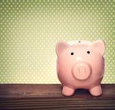 Sparschwein über grünem Tupfenhintergrund Stockbilder