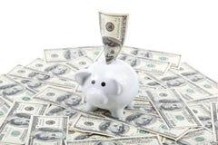 Sparschwein auf dem Hintergrund eines Stapels Dollarscheine Lizenzfreies Stockfoto