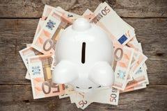 Sparschwein auf dem Stapel von Euros Lizenzfreie Stockfotografie