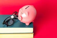 Sparschwein auf einem Stapel Büchern Stockfotografie