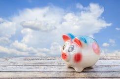 Sparschwein auf Holztisch über blauem Himmel verwischte Hintergrund Lizenzfreies Stockfoto