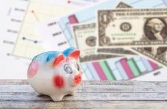 Sparschwein auf Holztisch über Dollar und Finanz- Papier-grap Lizenzfreie Stockbilder