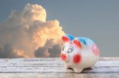 Sparschwein auf Holztisch über Himmel unscharfem Hintergrund Lizenzfreie Stockfotos