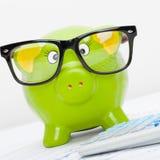Sparschwein in den Gläsern nahe bei einem Taschenrechner - nahe hohe Atelieraufnahme Stockfoto