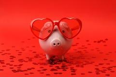 Sparschwein in der Liebe mit der roten Herzsonnenbrille, die auf rotem Hintergrund mit glänzendem rotem Herzen steht, funkelt Stockbild