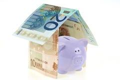 Sparschwein in einem Haus in den Banknoten stockfotos
