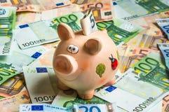 Sparschwein in einem Stapel des Eurogeldes Stockfotos