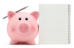 Sparschwein mit Übungsbuch und -bleistift auf weißem Hintergrund Stockbild