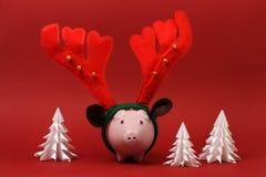 Sparschwein mit den Renhorn- und -klingelglocken, die auf rotem Hintergrund mit drei weißem Origamibäume Weihnachtshintergrund st Lizenzfreies Stockbild