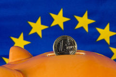 Sparschwein mit einer Euromünze, EU kennzeichnen im Hintergrund Lizenzfreies Stockfoto