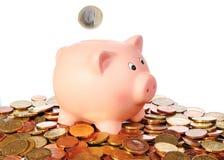 Sparschwein mit fallender Euromünze in einem Bereich von den Euromünzen Stockfotografie
