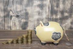 Sparschwein mit goldenen Metallmünzen stockfotografie