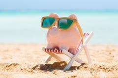 Sparschwein mit hölzerner Sonnenbrille auf dem Klappstuhl stockbilder