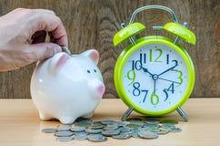 Sparschwein mit Münze und Wecker auf hölzernem Tabellenhintergrund Stockbilder