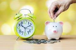 Sparschwein mit Münze und Wecker auf hölzernem Tabellenhintergrund Stockfotos