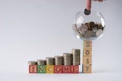 Sparschwein stellte auf Holzklötze Nr. 2017 mit Geschäftsmann ` s Hand ein, die Münze in Geldglas einsetzt Stockfotografie
