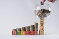 Sparschwein stellte auf Holzklötze Nr. 2017 mit Geschäftsmann ` s Hand ein, die Münze in Geldglas einsetzt Stockfoto