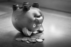 Sparschwein umgedreht auf Tabelle, Finanzproblemen und Schuldkonzept Lizenzfreie Stockbilder