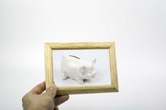 Sparschwein und ein hölzerner Beschaffenheitsrahmen Stockfotografie