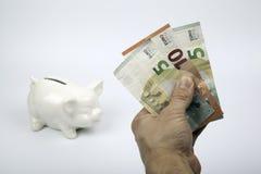 Sparschwein und Hand, die Geld auf weißem Hintergrund halten Stockfoto