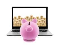 Sparschwein und Laptop mit Stapeln der goldenen Münzen Stockfotografie