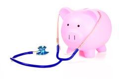 Sparschwein und Stethoskop lokalisiert auf weißem Hintergrund Lizenzfreie Stockfotos