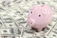 Sparschweinart-Geldkasten auf Hintergrund mit Geldamerikaner hundert Dollarscheine Stockbild