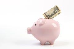 Sparschweinart-Geldkasten mit einem Dollar, der in Schlitz in einem weißen Studiohintergrund fällt Lizenzfreies Stockfoto