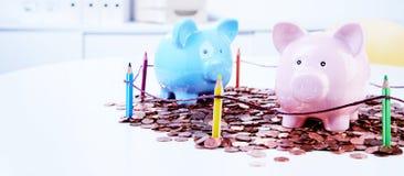 Sparschweine, die auf Stapel von Münzen stehen Lizenzfreies Stockbild